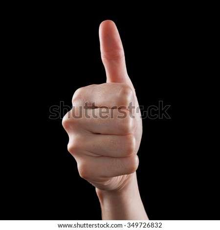 Approval thumbs up like sign as caucasian hand gesture isolated over black background