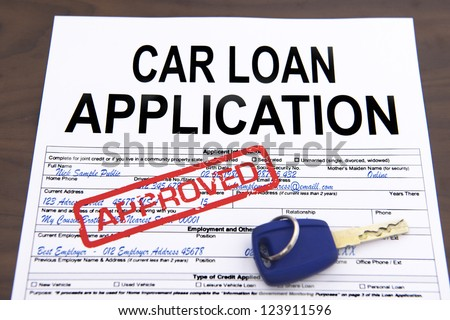 Approved car loan application form and key on desktop - stock photo