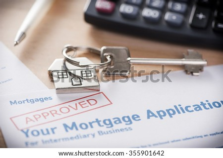 Approved mortgage loan agreement application with house shaped keyring - stock photo
