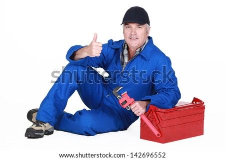 Approving tradesman posing with his tools - stock photo
