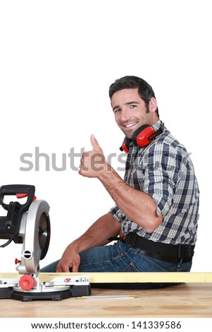 Approving tradesman using a mitre saw - stock photo