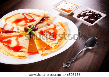 Apricot and strawberries jam on the homemade pancakes - stock photo