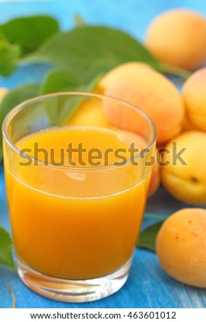 Apricot juice and ripe fresh apricots on the table