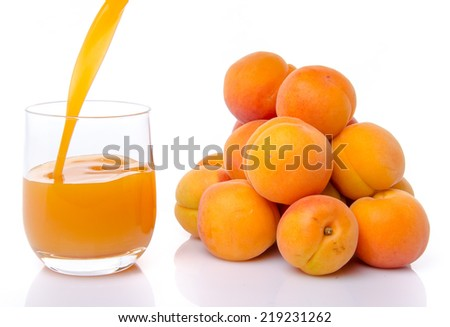 Apricot juice poured into a glass near a heap of apricots, isolated on white - stock photo