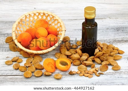 Apricot oil from  apricot kernels in a brown bottle , apricot seeds around  and  fresh apricots in a basket on wooden table