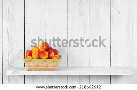 Apricots in a basket on a wooden shelf. - stock photo