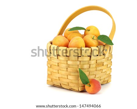 Apricots in basket with leaves on a white background