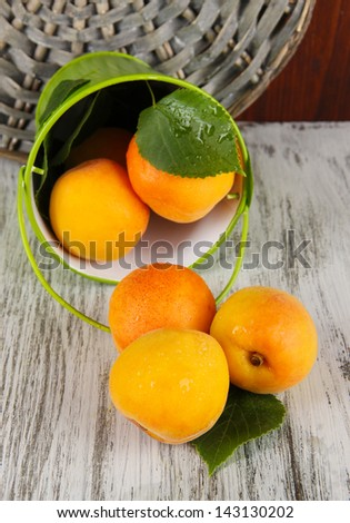 Apricots in bucket on wooden table near wicker coasters
