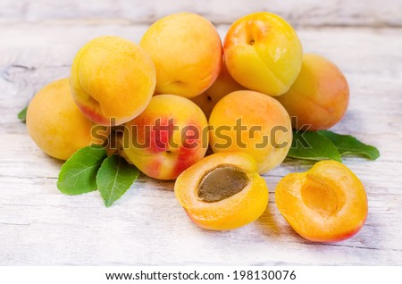 apricots on a white wood background. toning. selective focus on apricot with a stone. - stock photo