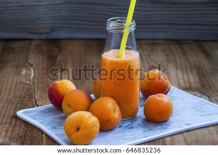Apricots smoothie bottle with straw and fruits