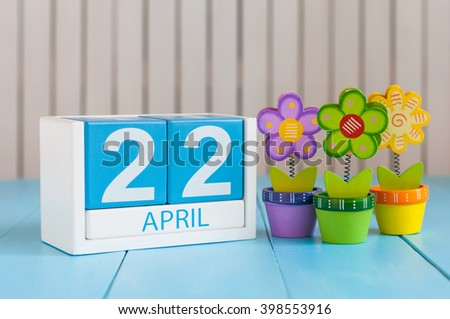 April 22nd. Earth Day. Image of april 22 wooden color calendar on white background with flowers. Spring day, empty space for text - stock photo