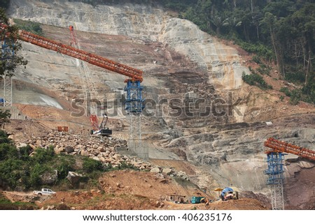 APRIL 6, 2016 : PAKXAN - LAO PDR : Under-construction of concrete dam with heavy equipment and cement conveyor structure and site landscape of Namngiep project in Pakxan District, LAO PDR.