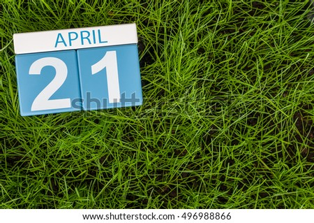 April 21st. Day 21 of month, calendar on football green grass background. Spring time, empty space for text