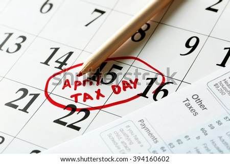 April tax day reminder in a calender  with tax form and pencil, close up - stock photo