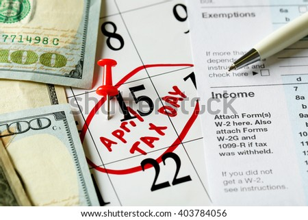 April tax day written and pinned in a calender, close up - stock photo