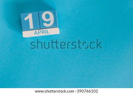 April 19th. Image of april 19 wooden color calendar on blue background.  Spring day, empty space for text. The Day Of Snowdrop - stock photo