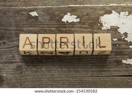 April word formed by wooden blocks on a wooden background - stock photo