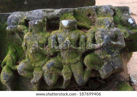 Apsara statue without head made by stone and covered by moss is placed outdoor - stock photo