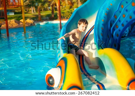 Aqua Park. The boy rolled down the hills in the pool - stock photo