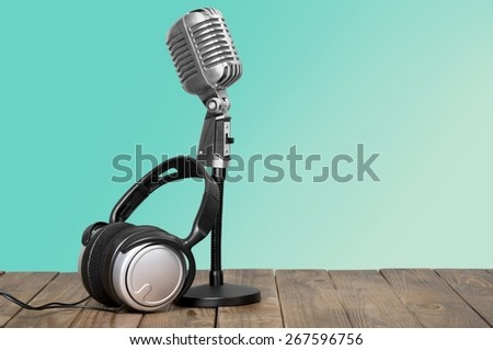 Aquamarine. Retro microphone and headphones on table - stock photo