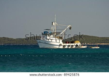 Aquamarine, white and green presenting white fishing boat - stock photo