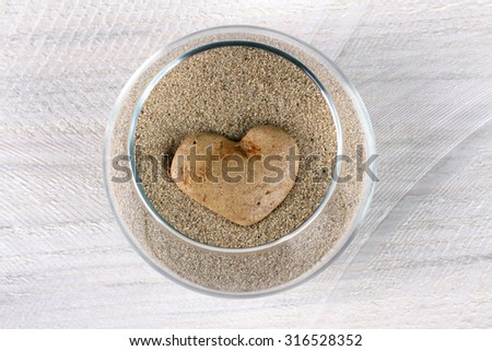 aquarium with sand and heart on wooden background - stock photo