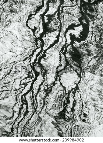 Aquatic abstract in autumn: Distorted reflection of bare trees on surface of stream, in black and white - stock photo
