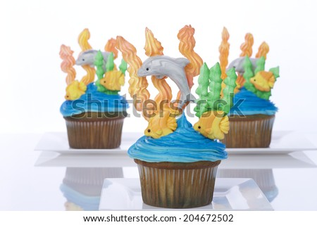 Aquatic under the sea themed cup cakes created at home with royal icing coral and sea weed marshmallow fondant dolphins and fish. Presented on white plates. Perfect for summer parties - stock photo