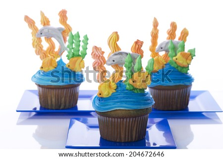 Aquatic under the sea themed cup cakes created at home with royal icing coral and sea weed marshmallow fondant dolphins and fish. Presented on blue plates. Perfect for summer parties - stock photo