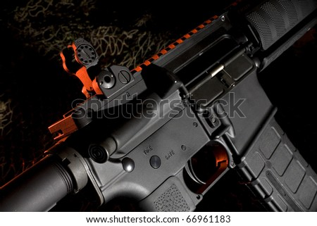 ar15 on a dark background with red highlights from behind - stock photo