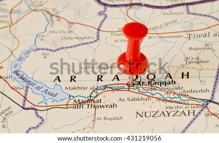 Ar-Raqqah marked on map with red pushpin. Selective focus on the word Ar-Raqqah and the pushpin. Pin is in an angle. Midground is sharp while foreground and background is blurry. - stock photo