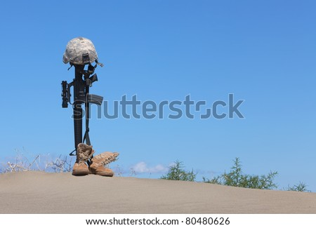 AR-15 rifle with combat helmet and boots as a memorial to a fallen soldier. - stock photo
