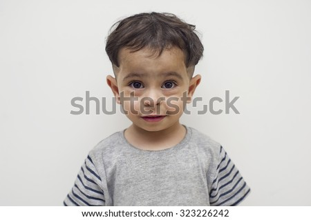 Arab boy smiling against a white background - stock photo