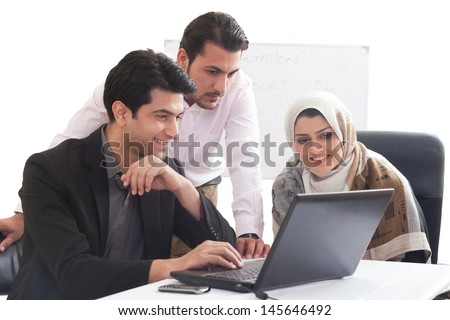 Arab business woman in a meeting with colleagues, three business people in the meeting, ethnic business people, business team. - stock photo