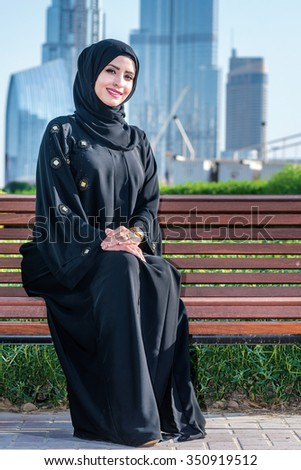 Arab businessman. Arab businesswoman hijab sitting on the bench on the background of skyscrapers in Dubai while smiling and looking directly at the camera. The woman is dressed in a black abaya - stock photo