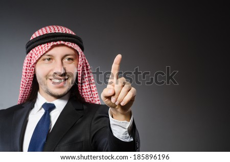 Arab businessman pressing virtual buttons against grey background - stock photo