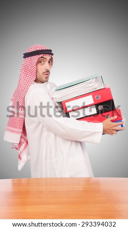 Arab businessman with many folders against gradient  - stock photo