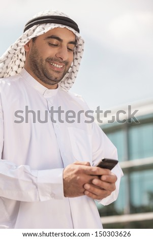 Arab businessman with mobile phone. Confident Arab businessman holding his mobile phone and smiling - stock photo