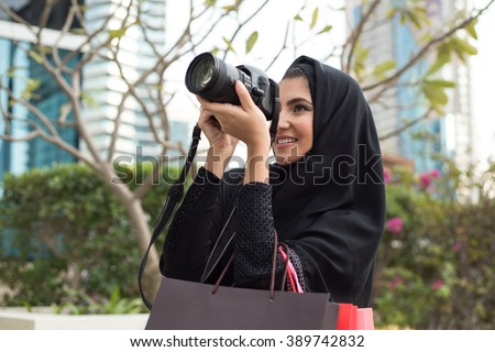 Arab Emirati Girl Taking Photos with a Photo Camera - stock photo