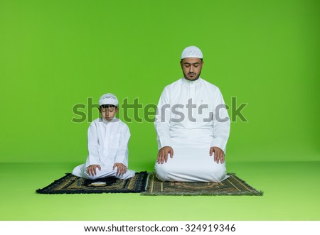 Arab father with son praying - stock photo
