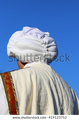 Arab man with white turban and blue sky - stock photo