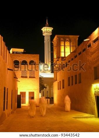 Arab men, in the old merchant quarter of Bastakiya in Dubai, walking to their mosque for evening prayer. - stock photo