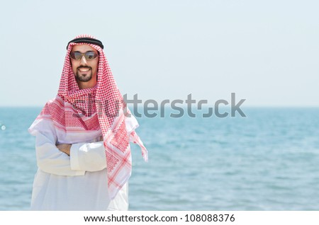 Arab on seaside in traditional clothing - stock photo