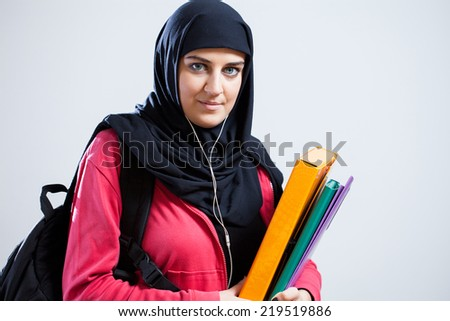 Arab student wearing head cover holding folders - stock photo