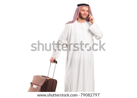 Arab tourist carrying a suitcase and talking on a mobile phone isolated on white background