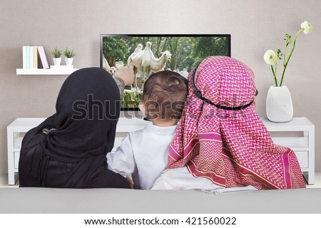 Arabian family sitting on the sofa while watching television together in the living room - stock photo