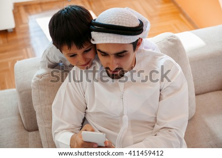 Arabian Father And Son Relaxing At Home Using a Smartphone At Home