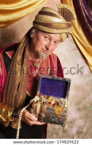 Arabian Genie bringing a treasure chest with gold and jewelry - stock photo