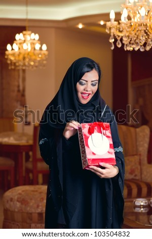arabian lady wearing hijab happy for receiving a gift - stock photo