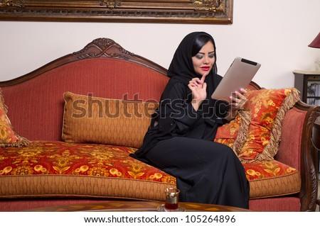arabian lady with hijab using Pad at home - stock photo